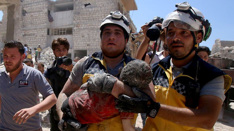 Members of the Syrian civil defence, known as the White Helmets, pull out an injured but alive child from under the rubble following a Russian air strike on Maaret al-Numan in Syria's north-western Idlib province on July 22, 2019
