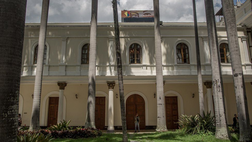 A view of the National Assembly building with a poster of Hugo Chávez's eyes