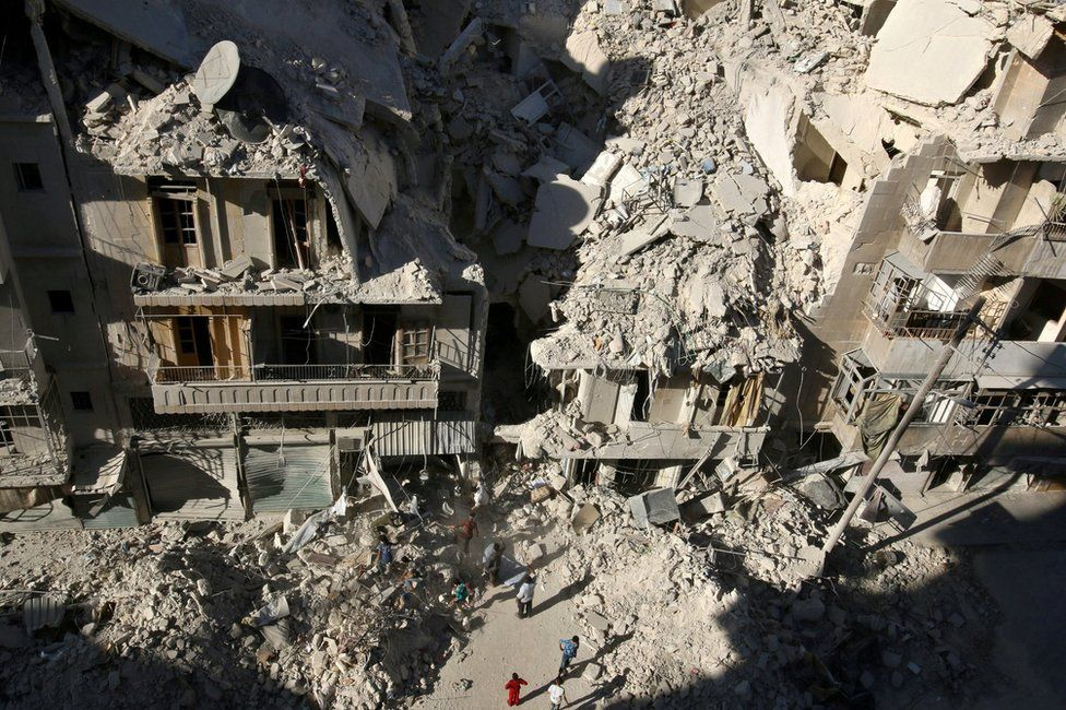 People search for survivors at the site of a reported air strike Tariq al-Bab, Aleppo, Syria on 26 September 2016