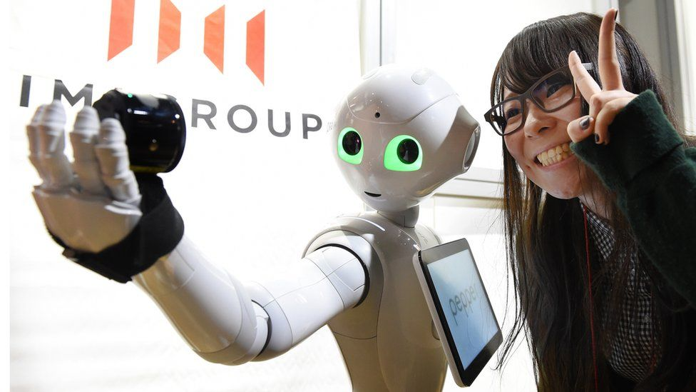A woman poses as humanoid robot Pepper takes a picture at a booth of digital marketing company IMJ Corporation during the Pepper App Challenge 2015 in Tokyo on February 22, 2015. Mobile phone carrier Softbank, which developed the humanoid robot, held the application competition for Pepper on February 22.