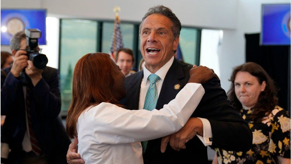 New York's governor hugs a hospital director at an event to lift 'virtually all' restrictions