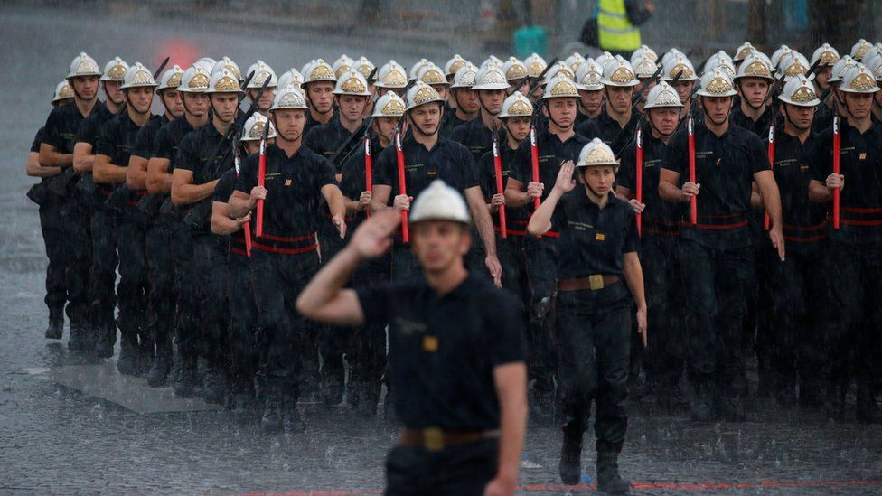 "French firefighters ""Pompiers de Paris"", walk under heavy rain on the Champs Elysees during a rehearsal of the traditional Bastille Day military parade in Paris, France, July 10, 2017"