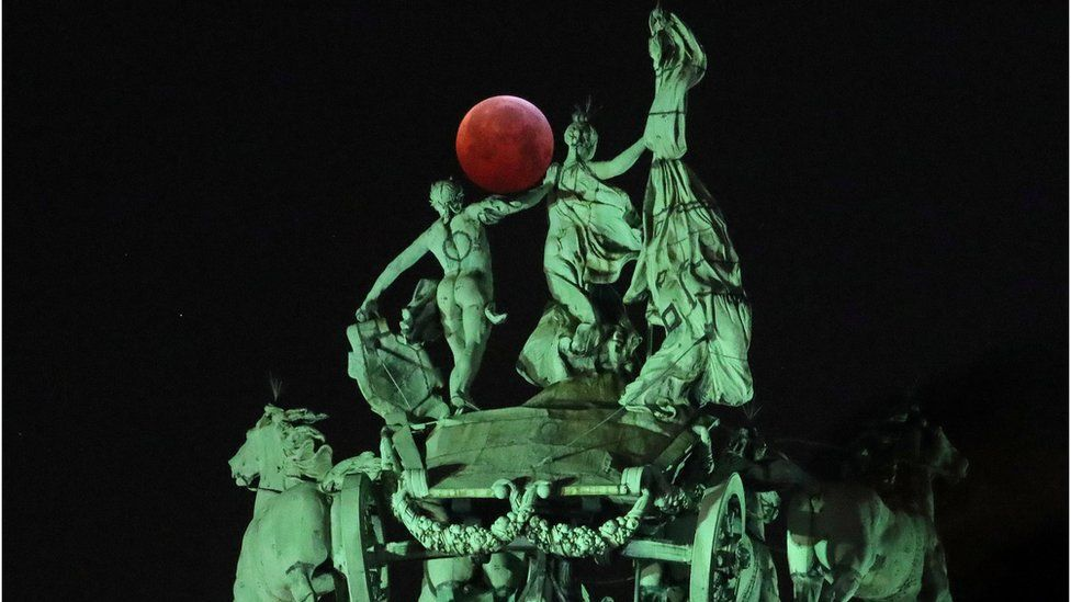 """The moon is seen beside a quadriga on the top of the Cinquantenaire arch during a total lunar eclipse, known as the """"Super Blood Wolf Moon"""", in Brussels"""