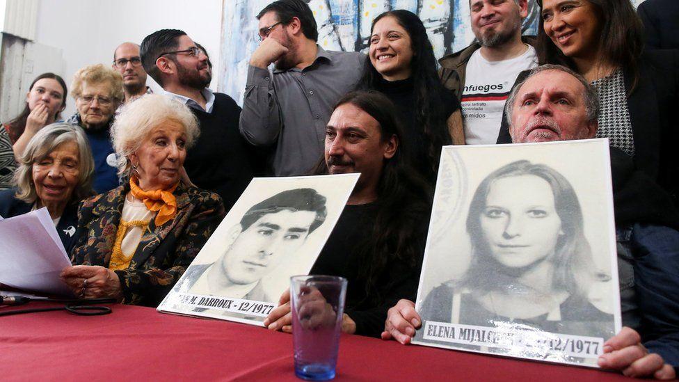 Mr Darroux, his uncle Roberto and Estela de Carlotto, president of Grandmothers of Plaza de Mayo, hold up photos of Mr Darroux's parents