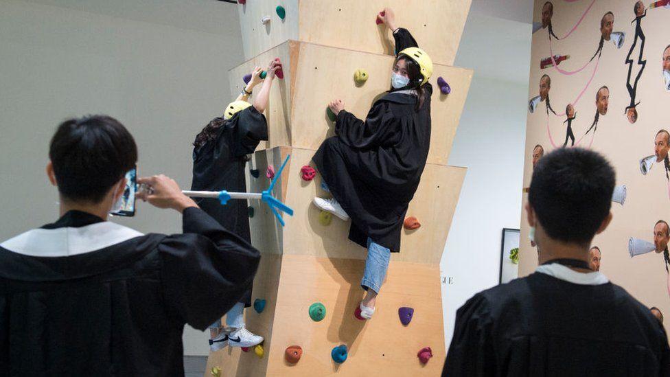 Woman climbing wall wearing a mask
