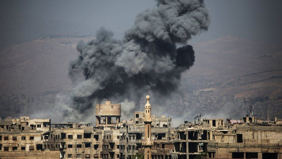 Smoke rises from buildings following an air strike on the rebel-held town of Ayn Tarma, in Syria's Eastern Ghouta area, on July 7, 2017