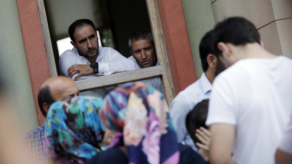 Forensic Medical Centre officials look out on family members who had gathered to hear news