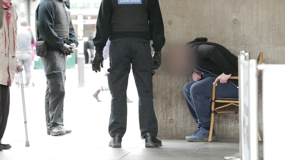 PCSOs with a man sat bent over in chair on street
