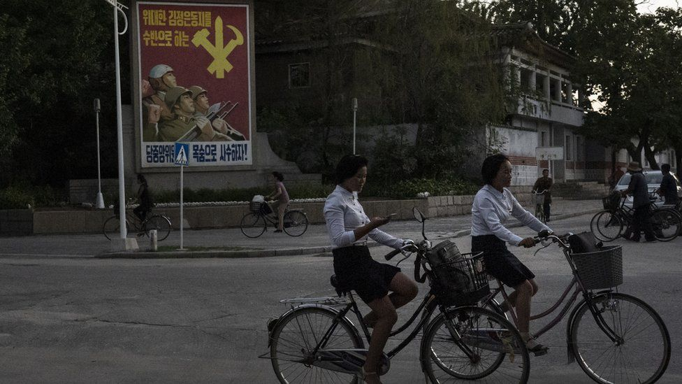 Girl checks her mobile phone while riding her bicycle