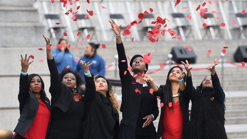 Members of London Community Gospel Choir throw poppies in Trafalgar Square, London, on 11 November 2015