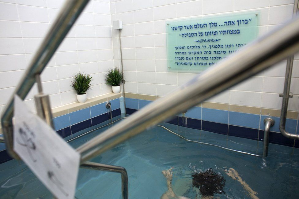 A Jewish woman enters the water of a mikveh in Jerusalem on April 17,2019. (Photo by Heidi Levine for The BBC).