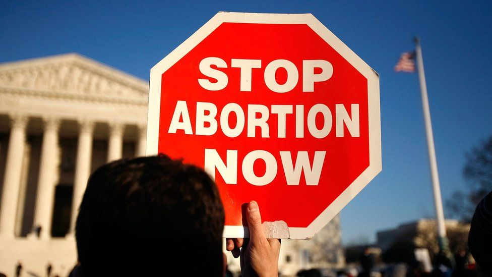 An anti-abortion campaigner holding up a sign reading 'stop abortion now', outside the US Supreme Court