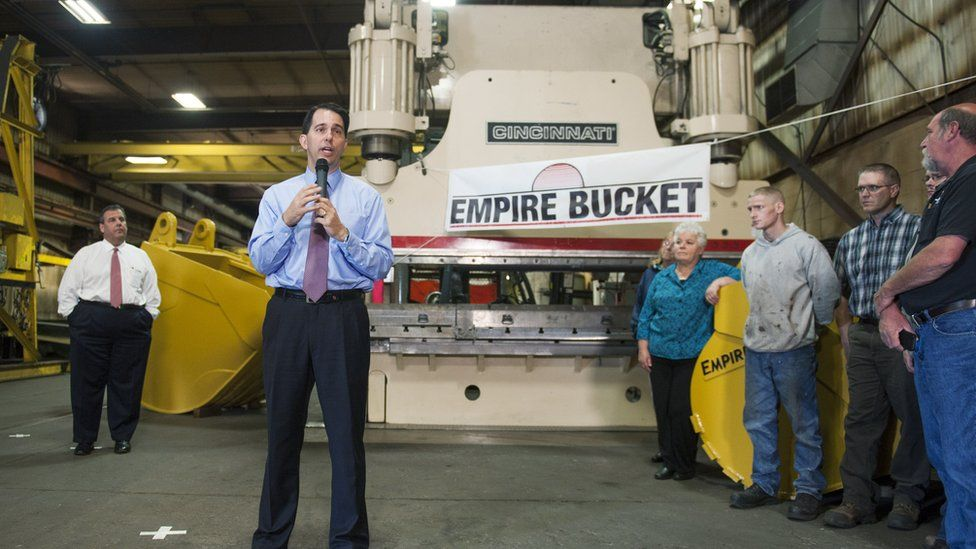Wisconsin Gov. Scott Walker (2nd L) speaks as New Jersey Gov. Chris Christie (L) listens during a campaign stop at Empire Bucket, a manufacturing facility September 29, 2014 in Hudson, Wisconsin.