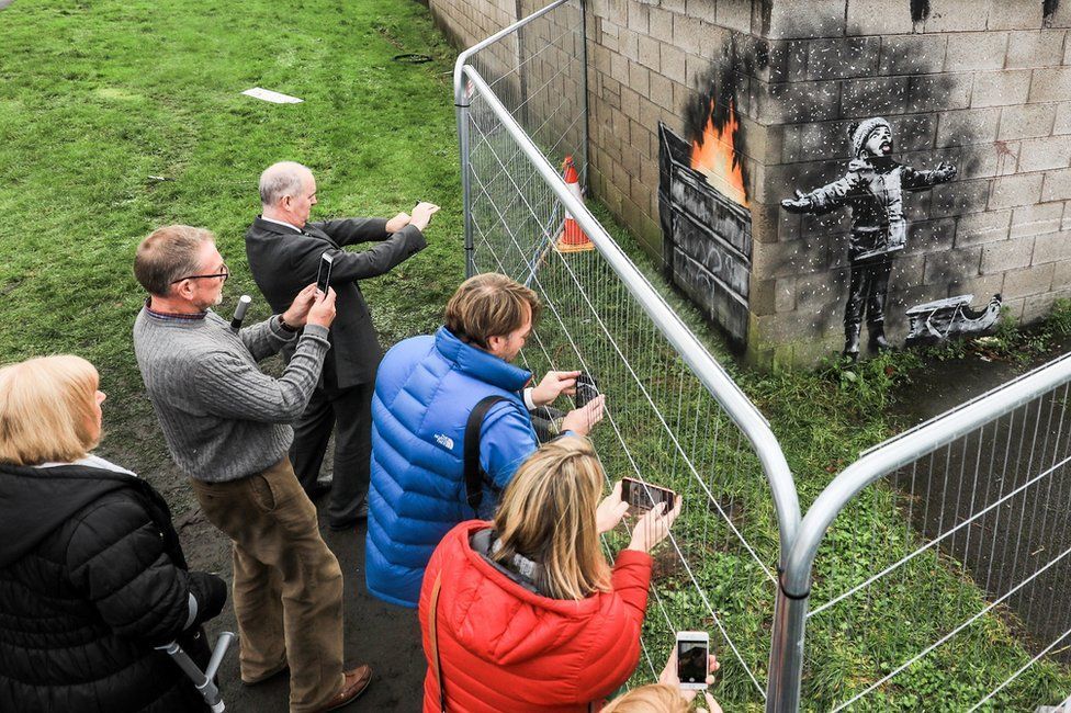 People gather around fences that have been erected to protect the latest piece of artwork by guerrilla artist Banksy on 20 December 2018