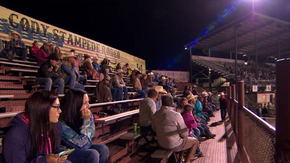 Spectators at rodeo sit on benches