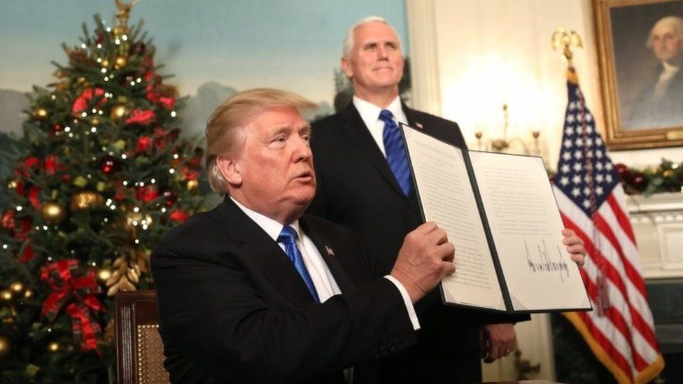 US Vice-President Mike Pence watches (right), as Donald Trump holds up his proclamation on Jerusalem's policy. Photo: 6 December 2017