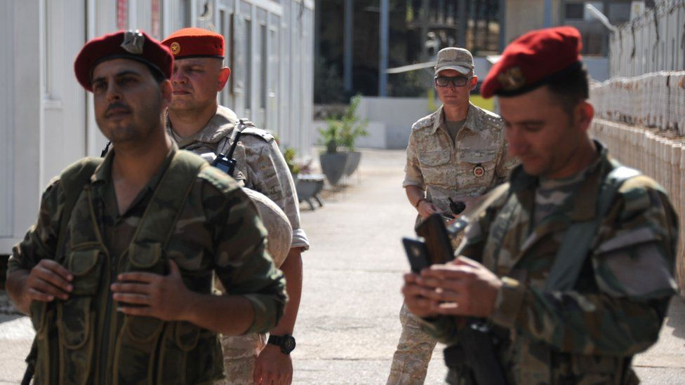 Russian soldiers, standing behind these two Syrian soldiers are part of the Russian force at the naval base at Tartus