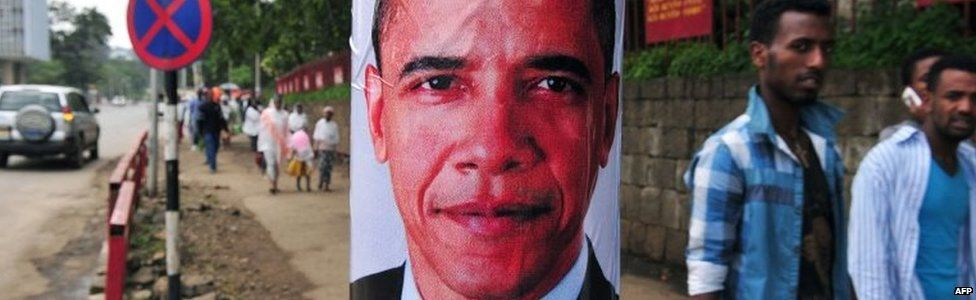 Pedestrians walk past a poster of US President Barack Obama before his arrival in Addis Ababa on 26 July 2015