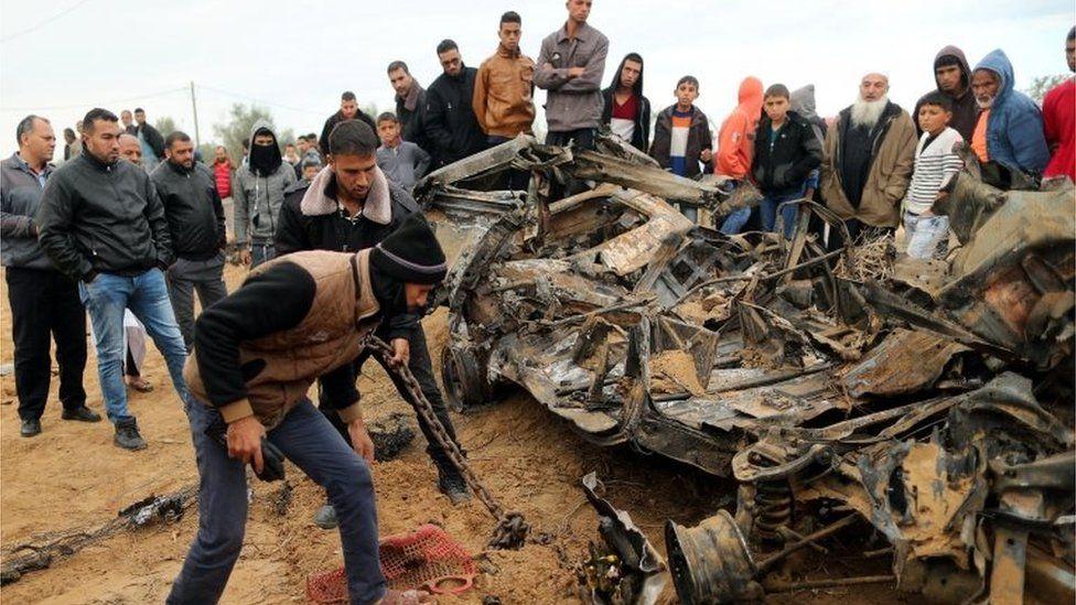 Palestinians look at wreckage of car destroyed in Israeli air strike in Khan Younis (12/11/18)
