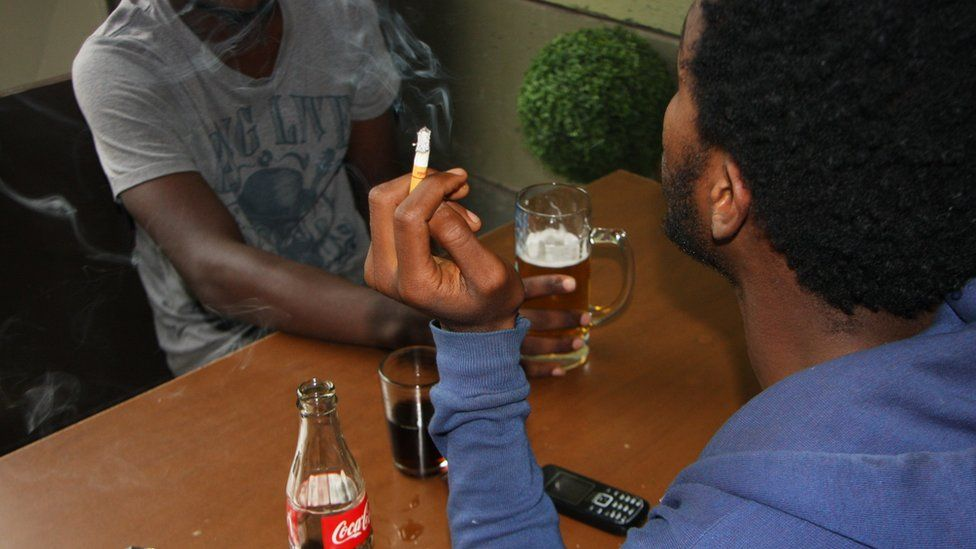 Inside a small bar off Bole Road 22-year-old Daniel smokes with his friend