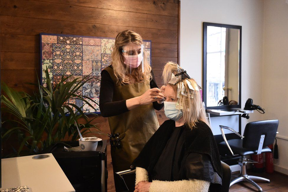 A customer receives a haircut in a salon