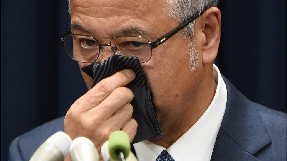 """Japan""""s Economy Minister Akira Amari wipes his nose during a press conference in Tokyo on January 28, 2016."""