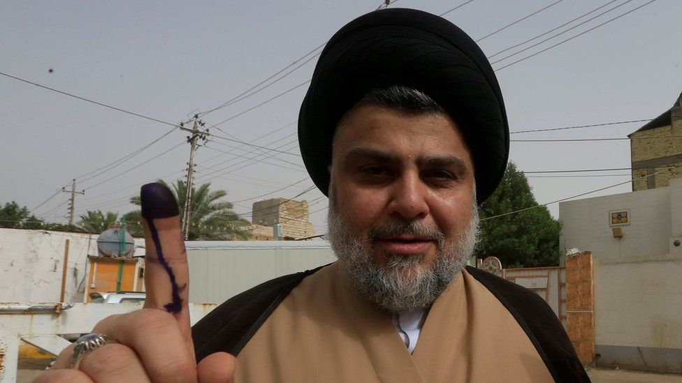 Iraqi Shia cleric Moqtada al-Sadr shows his ink-stained finger after casting his vote at a polling station during the parliamentary election in Najaf on 12 May 2018