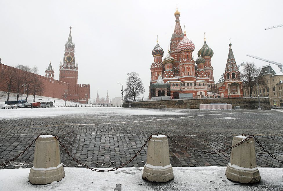 The clock on Spasskaya tower showing the time at noon, is pictured next to Moscow's Kremlin, and St. Basil's Cathedral