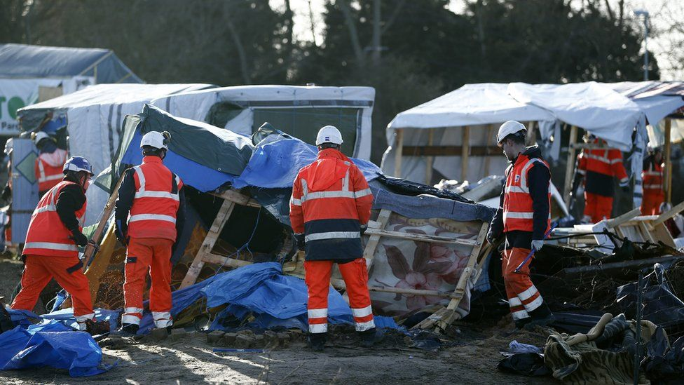 """Workers demolish a shelter in the migrant camp, the """"Jungle"""", in Calais, France, 2 March 2016"""