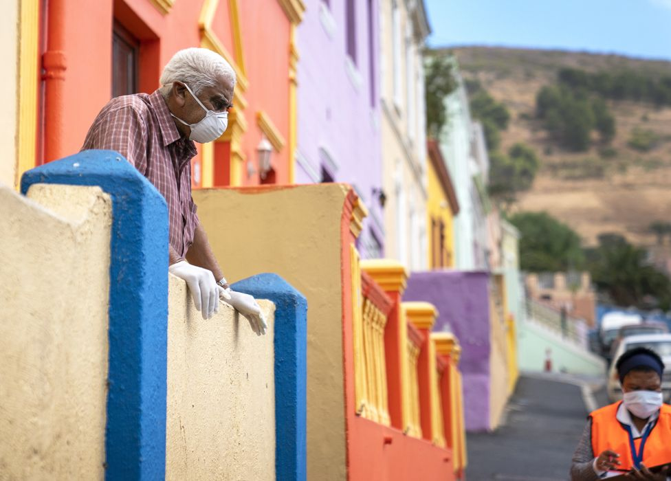 A man in a mask looks down at a health worker in Bo-Kaap, Cape Town, South Africa - Tuesday 7 April 2020