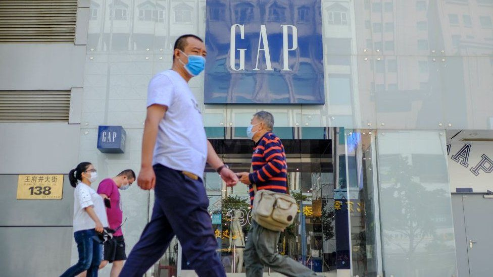 Customers walk outside a GAP store with protective masks in Beijing, China.