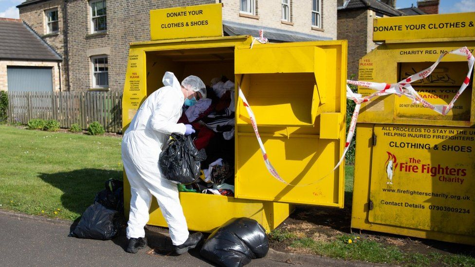 Person in forensic suit looking through recycling bin