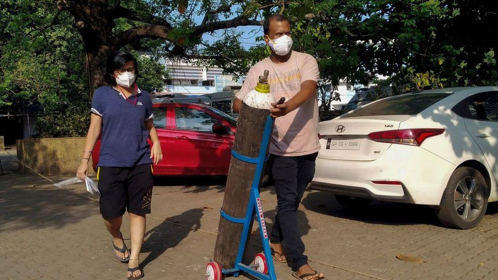 A couple walks with an oxygen cylinder for a Covid-19 coronavirus patient admitted at the Goa Medical College and Hospital.