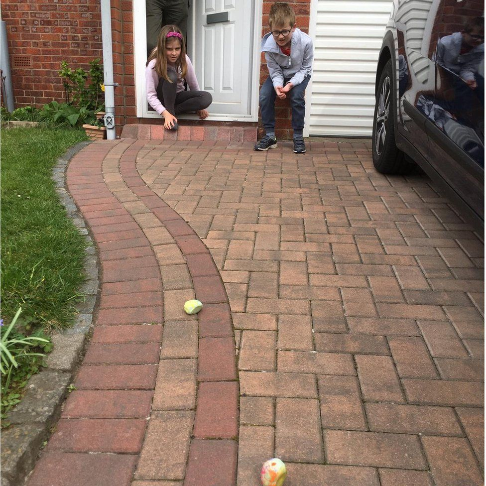 Naomi Leathes, 9, and Daniel Leathes, 7, rolling their eggs down the drive at their Edinburgh home on Easter Sunday