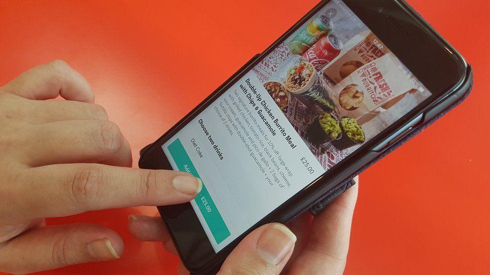 Hands shown using Deliveroo app