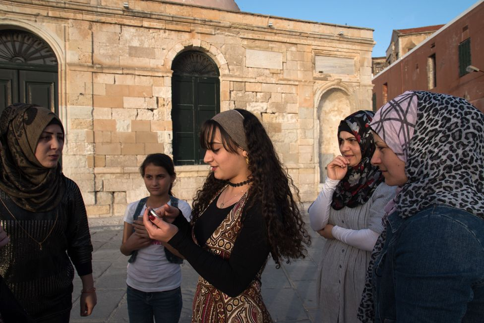 "Esraa Afandaki, 16, in the center, along with her sister Fatima,21, Reem Tarzalaki,11, Yasmin Afandaki,32,and Faten Tarzalakis, 36 go for an afternoon walk at Chania harbor. Behind them lie Giali Tzamisi, an imposing mosque in the harbor, that used to be one of the earlier buildings of the Ottomans in Crete. It is called Giali Tzamisi, which means ""The Seaside Mosque"", because it was built next to the sea."