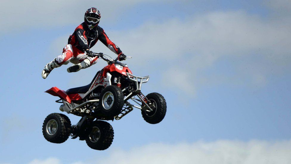 A quad bike rider does a stunt at Balmoral Show