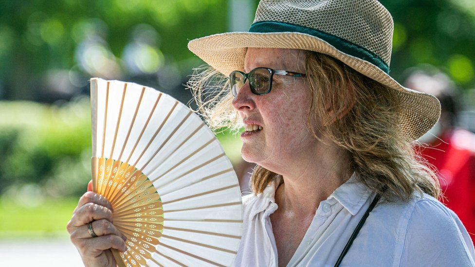 A woman cooling down with a fan on a hot and humid day in London