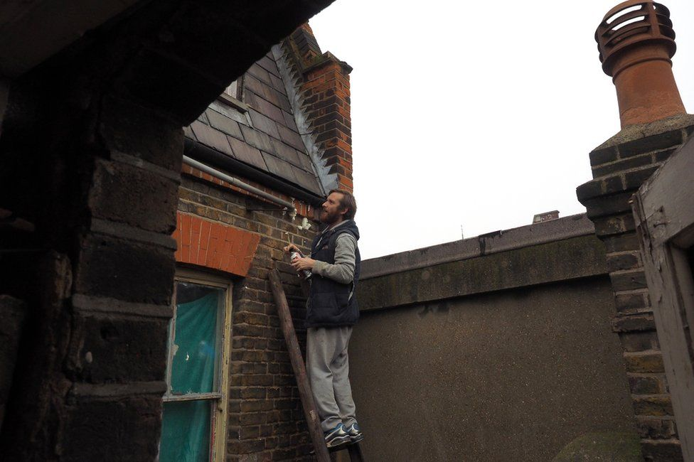 A man on a ladder against the outside of the building