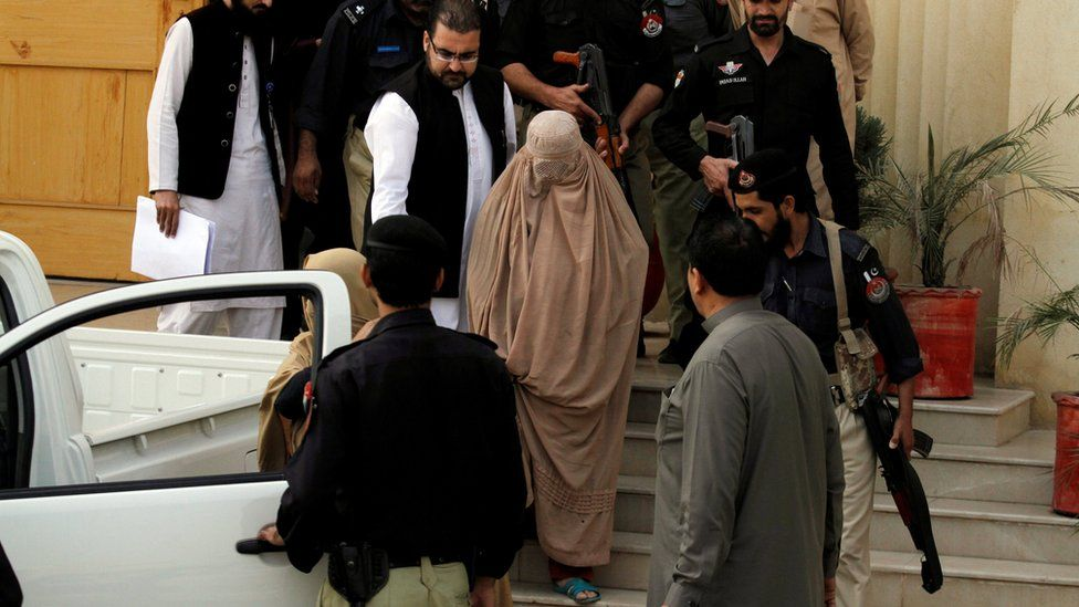 Policemen escort Sharbat Gula (C) as she leaves after appearing before a court in Peshawar, Pakistan, November 4, 2016