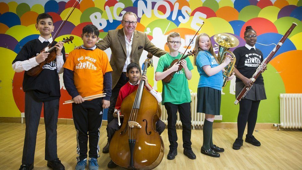 Benny Higgins with some of the children who are learning to play an instrument