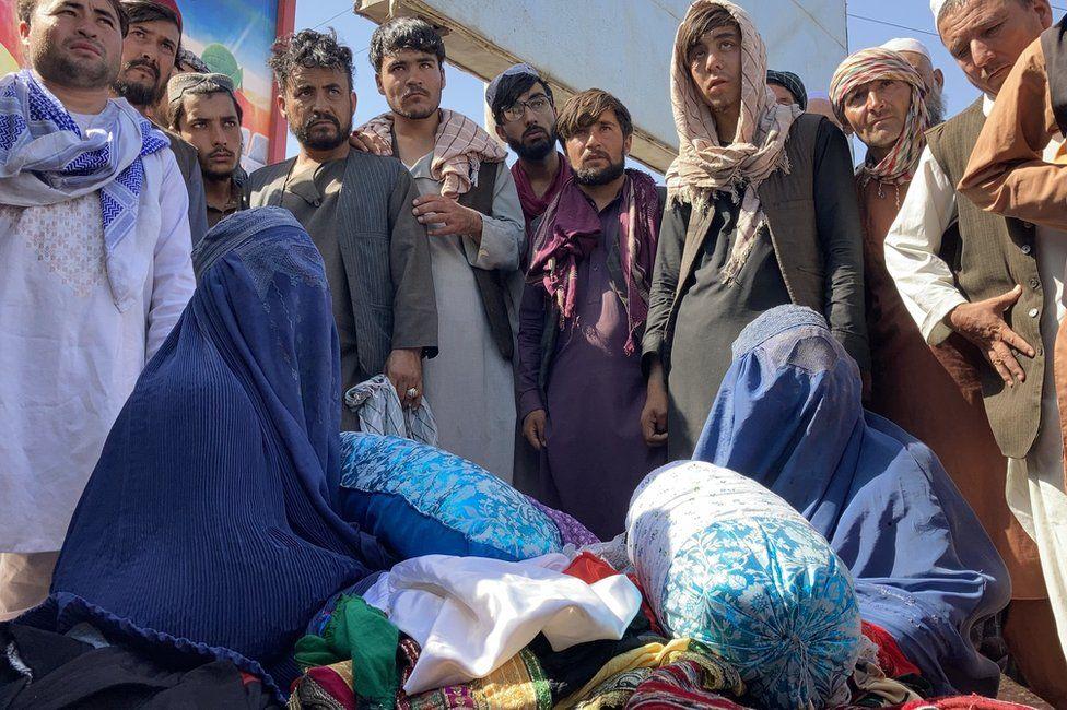 "Shagufta at the market in Mazar-i-Sharif. ""I am selling my children's finest clothes,"" she said."