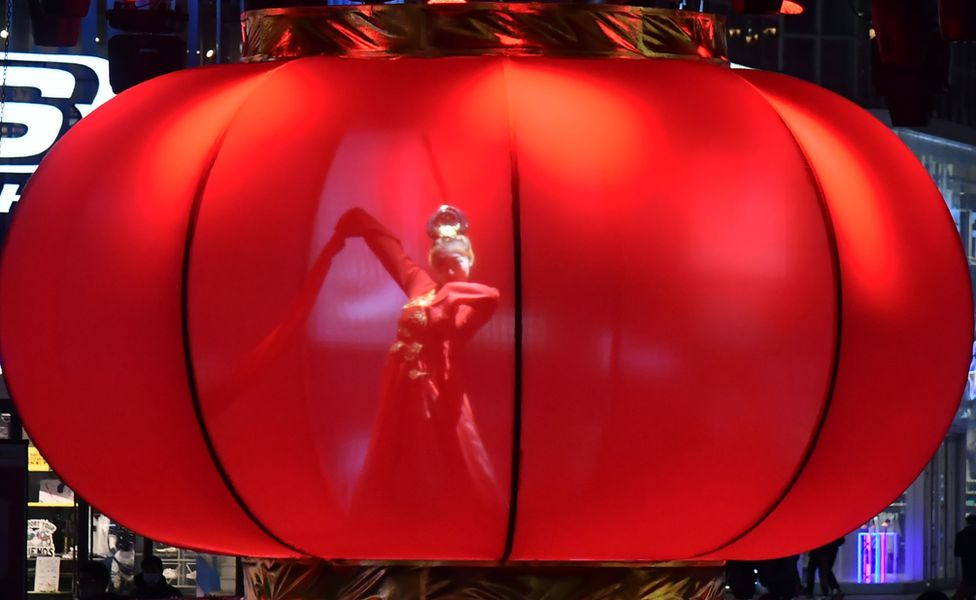 A woman dances inside a huge red lantern in Shenyang, north-eastern Liaoning province. Photo: 26 February 2021