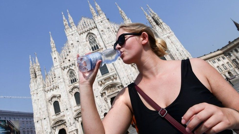 A woman drinks water in hot Milan, 26 June
