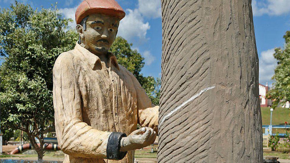 Escultura de un hombre sacando la sabia de un árbol