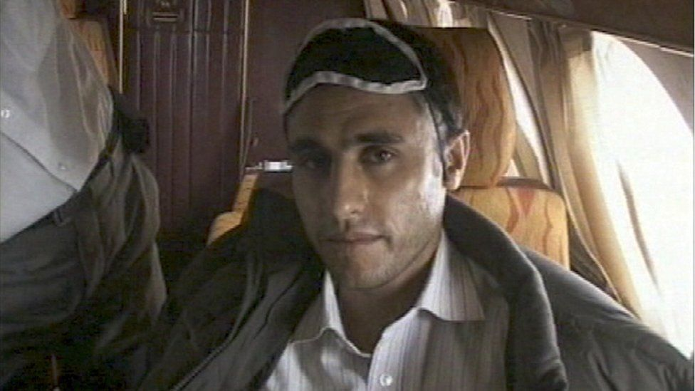 This frame grab released February 23, 2010 from Iranian state TV shows Sunni Muslim rebel leader Abdolmalek Rigi under armed guard following his arrest. Rigi is on board a small plane.
