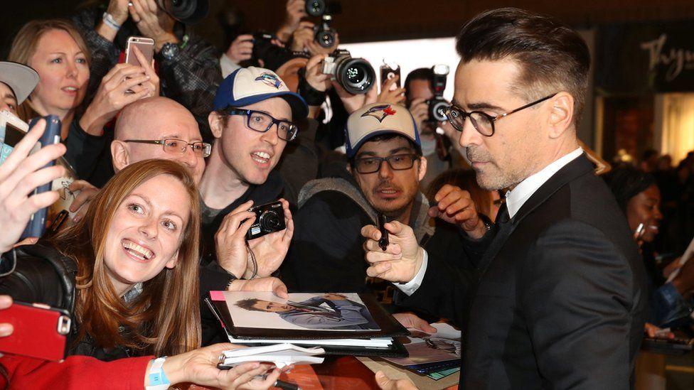 Colin Farrell signs fan memorabilia on the red carpet