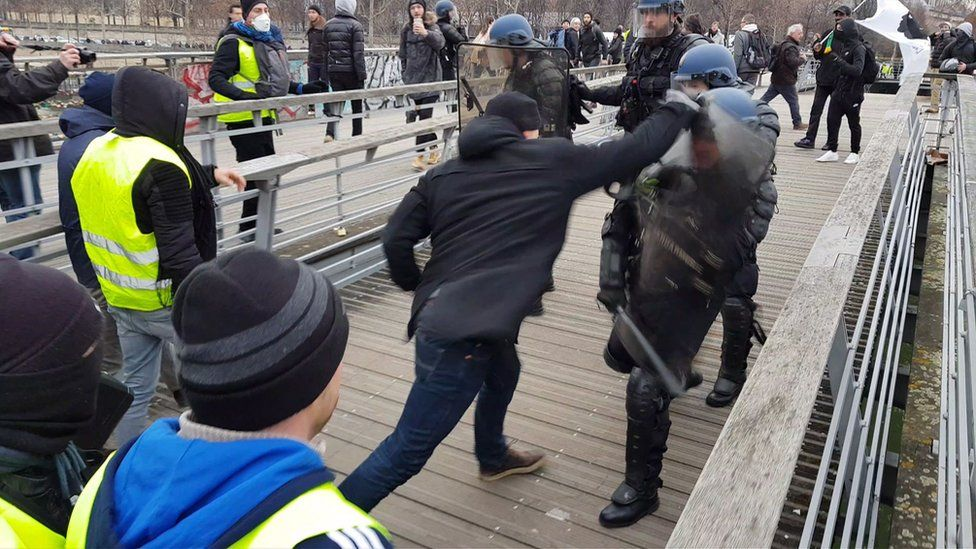 """A man in a boxing stance fights riot police during a demonstration by """"Gilets Jaunes"""" anti-government protesters on a bridge leading to the National Assembly in Paris on January 5, 2019"""