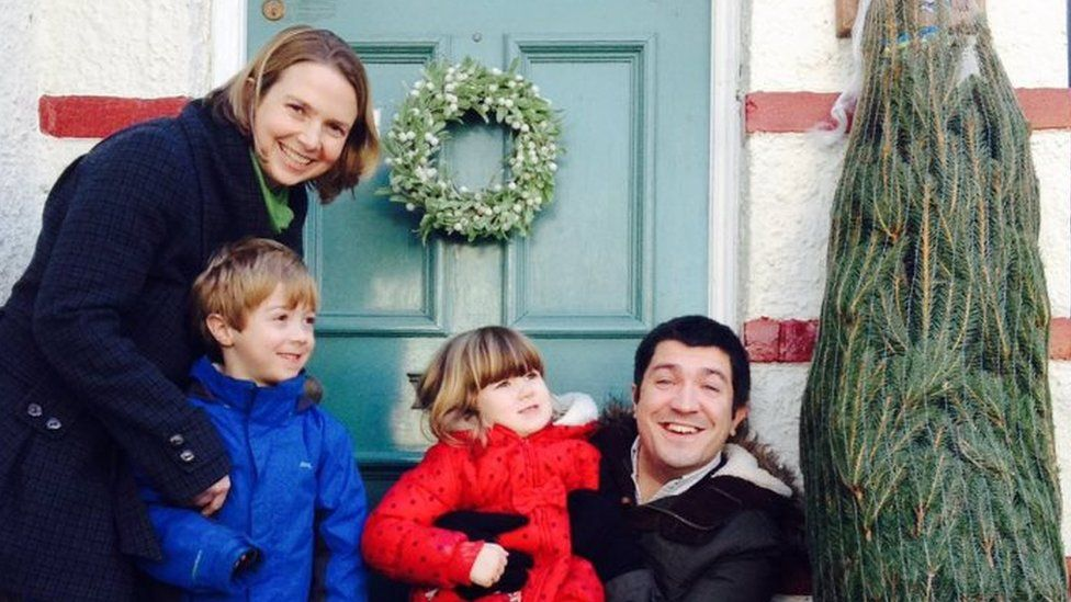 The Wilsons outside their front door with a Christmas tree