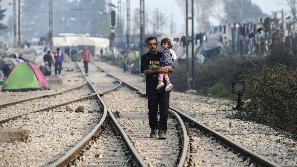 A migrant man holds his daughter at a camp on the Greek-Macedonian border